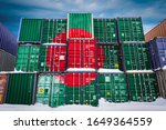 The national flag of Bangladesh on a large number of metal containers for storing goods stacked in rows on top of each other. Conception of storage of goods by importers, exporters