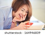 asian teenage laughing while... | Shutterstock . vector #164946839