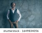 Small photo of Portrait of stunning rich wealthy old millionaire dandy man look copy space put hands pocket wear shirt brown trousers outfit isolated over concrete wall grey color background