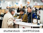 Small photo of Strasbourg, France - Feb 16, 2020: Customer talking about French wine at the Vignerons independant English: Independent winemakers of France wine fair for private and horeca customers