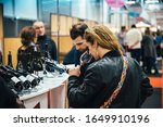 Small photo of Strasbourg, France - Feb 16, 2020: Rear view of confident woman tasting red French wine at the Vignerons independant English: Independent winemakers of France wine fair for private and horeca