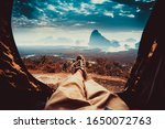 POV view of hipster tourist inside tent on front of mountains and sea. Adventure travel lifestyle wanderlust - stock photo