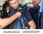 Small photo of Diving instructor helps a beginner diver prepare for diving. diver helps another diver equip young guy, checks his equipment. A team of human divers is preparing for the dive checking the equipment