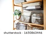 Small photo of Spring cleaning of closet. Vertical tidying up storage. Neatly folded bed sheets in the metal black baskets for wardrobe. Nordic style.