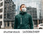 Small photo of portrait of brunette man in a surgical bandage on a background of a modern building, coronavirus, illness, infection, quarantine, medical mask