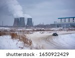 "Small photo of Russia, Novosibirsk - November 30, 2019. Russian old dark car ""VAZ-Zhiguli"" quickly goes drifting, lifting snow behind him on the turn for the pipes of the thermal power plant in winter."