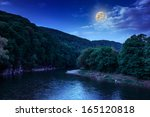 river flows by rocky shore near the autumn mountain forest at night - stock photo