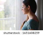 Small photo of COVID-19 Pandemic Coronavirus Woman home isolation. Melancholic sad woman with low gaze at home in a rainy day, focus on the model eyes, indoor photo.