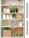 White Shelving Unit With Plant...
