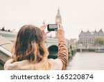 young woman taking a photo with ... | Shutterstock . vector #165220874