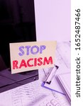 Small photo of Text sign showing Stop Racism. Conceptual photo end the antagonism directed against someone of a different race Note paper taped to black computer screen near keyboard and stationary.