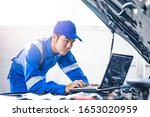 Close up concept of male asian car mechanic using a computer laptop to diagnosing and checking up on car engines parts for fixing and repair, working on the car engine wearing blue overall and a hat - stock photo