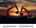 Two Excavators Are Digging The...