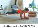 Small photo of Young beautiful athletic girl in leggings and top makes an exercise plank. Healthy lifestyle. A woman goes in for sports at home.