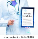 hands of doctor with tablet... | Shutterstock . vector #165430109