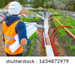 Small photo of Laying utilities. Man looks at the pipes leading to the well. Builder with drawings next to the water supply. Pipes at the construction site lead. Human in a construction uniform looks at water pipes