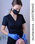 Small photo of portrait in the cosmetologists office. A young girl in a medical suit, gloves and a syringe performs an injection into the facial and neck muscles to treat wrinkles. scars, muscle spasm, torticollis