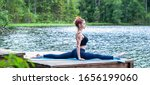 Small photo of Young yogi girl practicing yoga, stretching in Monkey God exercise, Splits, Hanumanasana pose on the lake. The concept of appeasement, healthy lifestyle.