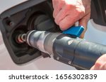 Detail of an old man's hands holding the hose while refueling compressed natural gas (CNG) in an ecological car. Clean energy concept. - stock photo