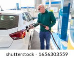 Old man in a green sweater and jeans, filling up with gas in his white ecological car. Filling the tank with compressed natural gas (CNG). Sustainable energy concept. - stock photo