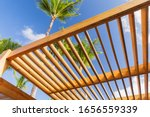 Small photo of Wooden sunshade roof structure fragment under blue sky at sunny summer day, palm trees are on a background