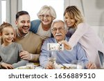 Small photo of Happy extended family using smart phone taking selfie with smart phone in dining room.