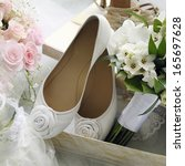 Bridal bouquet and bride shoes with roses. - stock photo