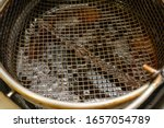 Small photo of Dirty grate in deep fryer. Dark brown oil inside. Fast food. Health hazards, fatty foods. Obesity problems. Untimely replacement, bad faith. Blur at the edges.