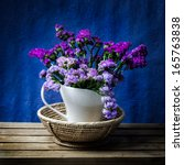 Bunch of purple flower decorated in classic white vase on wooden table with dark blue background - stock photo