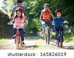family on cycle ride in... | Shutterstock . vector #165826019