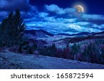 pine trees near valley in mountains and autumn forest on hillside under blue sky with clouds at night - stock photo