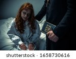 Small photo of exorcist holding bible and hugging demoniacal girl in bedroom
