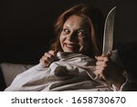 Small photo of demoniacal smiling girl holding knife in bed