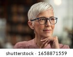 Small photo of Beautiful senior business woman thinking and wearing spectacles. Thoughtful old woman teacher looking away with eyeglasses. Closeup face of mature pensive lady contemplating the future with copy space