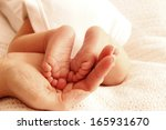 a mom holds the legs of cute... | Shutterstock . vector #165931670