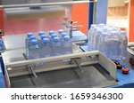 Small photo of Shrink film wrapping machine for package bottle of water. Food industry