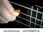 Bass Guitar Player With Pick I...