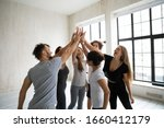 Small photo of In modern studio gather cheerful multi-ethnic happy excited people in sportswear giving high five stacked palms together express unity feeling amity showing support, common sport goal achieved concept