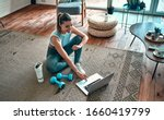 Small photo of A sporty woman in sportswear is sitting on the floor with dumbbells and a protein shake or a bottle of water and is using a laptop at home in the living room. Sport and recreation concept.
