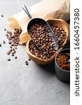 Small photo of Coffee beans in a wooden bowl made of olive wood, in a paper bag, a metal scoop and ground coffee on a light gray background. Space for text.