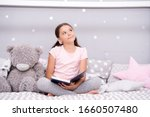 Small photo of Story that grabs imagination. Little girl read and imagine. Cute dreamer with book and toy. Kids imagination and fantasy. Reading feeds imagination. Inspiring child imagination.