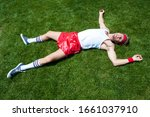 Small photo of Exhausted geek athlete lying splayed out on green field