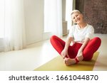 Small photo of Sporty 50 year old gray haired woman sitting barefooted on yoga mat indoors doing bound ngle pose which helping to relieve symptoms of menopause. Aging, maturity, wellness and health concept