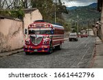 """Small photo of Antigua Guatemala - March 16, 2017: Colorful local """"chicken buses"""" wobbling on the cobbled street of Antigua Guatemala."""