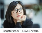 Small photo of Cloe up head and shoulders portrait shot of attactive young Asian woman wearing stylish eyeglasses resting chin on her hand looking away