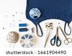 Small photo of Needlework and beadwork. Top view on process of decoration of a blue top with bugle embroidery. Accessories for embroidery: sets of beads and spangle in boxes, tweezers, needles and scissors