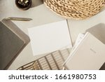 Flatlay blank paper sheet, notebooks, clips in wooden bowl, straw stand on beige concrete background. Home office desk workspace. Business, work template. Flat lay, top view.