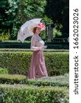 Small photo of Elegant lady, from high society of the twentieth century, walking through a public park