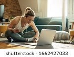 Small photo of Young happy athletic woman surfing the net on laptop while taking a break from exercising at home.