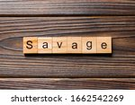 Small photo of SAVAGE word written on wood block. SAVAGE text on wooden table for your desing, concept.